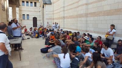 foto mons. Giulietti con giovani in Terra santa